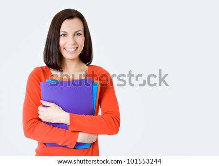 Young smiling student woman. Over gray background - stock photo