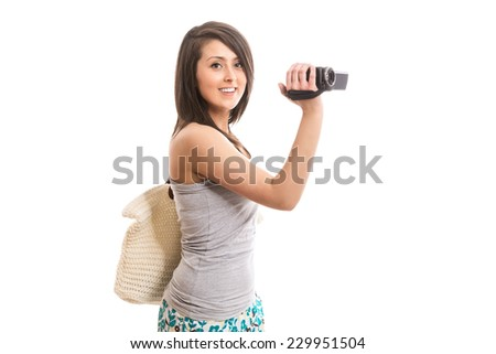 Young smiling tourist with video camera