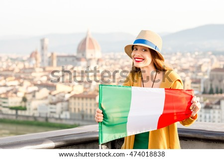 Young smiling traveler in yellow holding italian flag on the old town background in Florence in the morning. Promoting tourism in Italy.