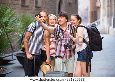 Young smiling travelers walking through the city and doing selfie - stock photo
