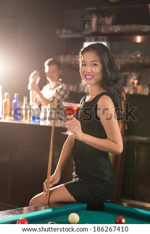 Young smiling Vietnamese woman sitting with a drink on the edge of pool table in the pub - stock photo
