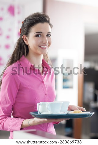 Young smiling waitress in pink shirt serving coffee at the bar, floral wallpaper on background - stock photo