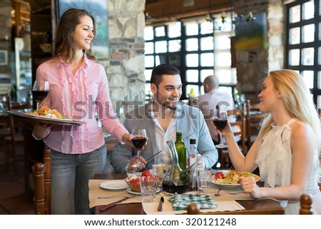 Young smiling waitress is serving a beautiful couple in a restaurant - stock photo