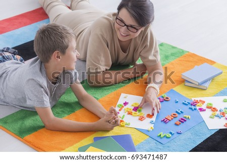 Young smiling woman and blonde kid solving puzzle on a colorful carpet on the floor