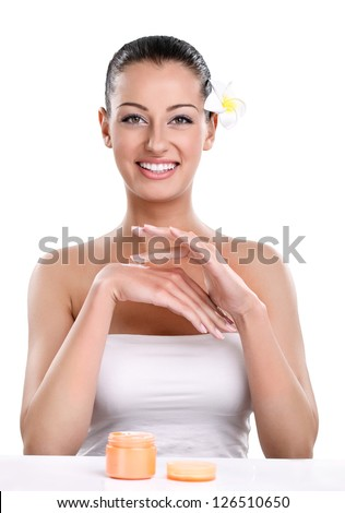 Young smiling woman applying cosmetic cream on hands - stock photo