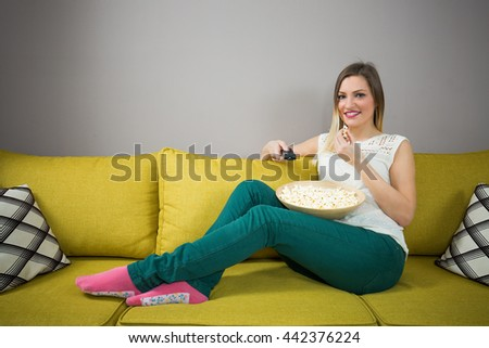 Young smiling woman at home sitting on the couch and watching tv, she is holding a remote control and eating popcorn - stock photo