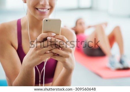 Young smiling woman at the gym relaxing and listening to music using a mobile phone and earphones - stock photo