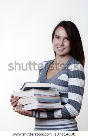 young smiling woman carrying books on white background