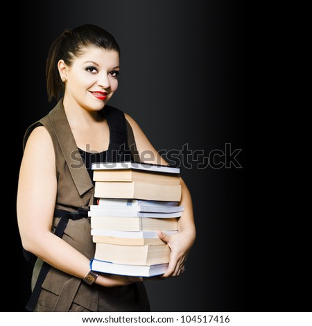 Young smiling woman carrying library books in a education and studying concept on dark background