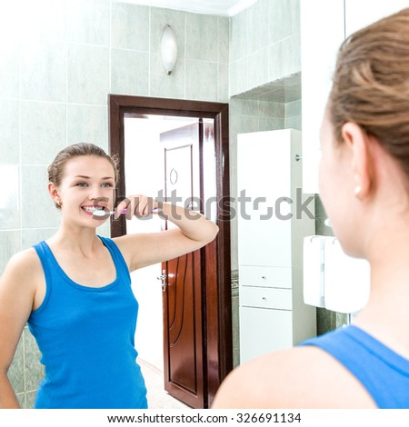 Young smiling woman cleaning teeth with toothbrush. Beauty and dental health concept. - stock photo