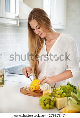 Young smiling woman cooking vegetables at the kitchen - stock photo