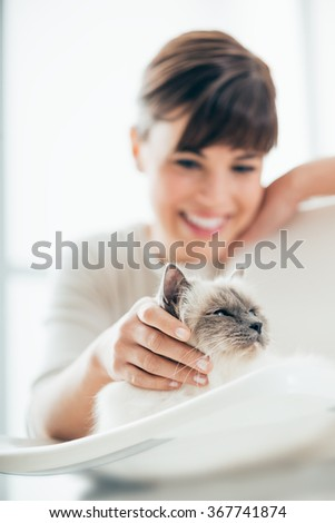 Young smiling woman cuddling her beautiful long hair cat lying on a chair, pets and lifestyle concept - stock photo