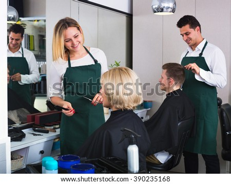 Young smiling woman cutting female pensioner hair in hairdressing saloon