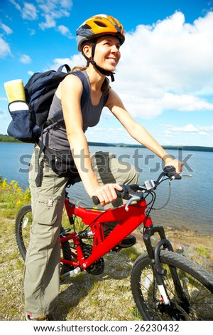Young smiling  woman cycling near the lake - stock photo