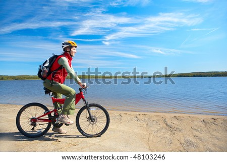 Young smiling  woman cycling near the lake