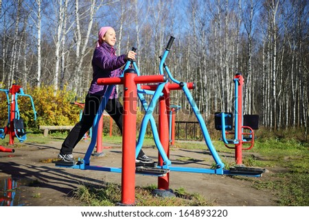 Young smiling woman does exercises at simulator in park in autumn sunny day. - stock photo