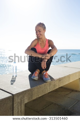 Young smiling woman dressed in sportswear enjoying rest after morning run while sitting on a pier against sea and sky, happy female runner relaxing after fitness training in the fresh air in sunny day - stock photo
