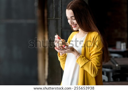 Young smiling woman dressed in yellow sweater eating ice cream in the dark cafe interior - stock photo