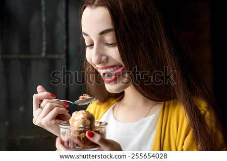 Young smiling woman dressed in yellow sweater eating ice cream in the dark cafe interior