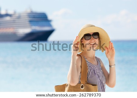 young smiling woman enjoying beach vacation with cruise ship in the background - stock photo