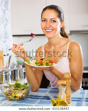 Young smiling woman enjoying vegetable salad and smiling