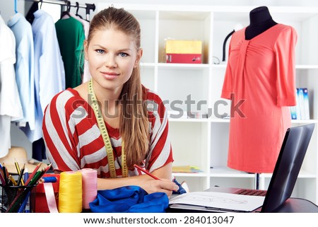 Young smiling woman entrepreneur sitting with textile, thread and laptop at the desk in her own fashion studio.