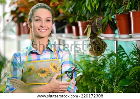 Young smiling woman florist working in the greenhouse. - stock photo
