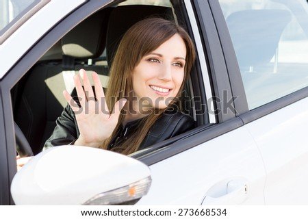 Young smiling woman greeting with hand from car. Cheerful caucasian girl welcome somebody sitting in automobile - stock photo
