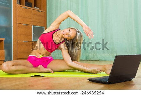 Young smiling woman having pilates class with notebook indoor  - stock photo