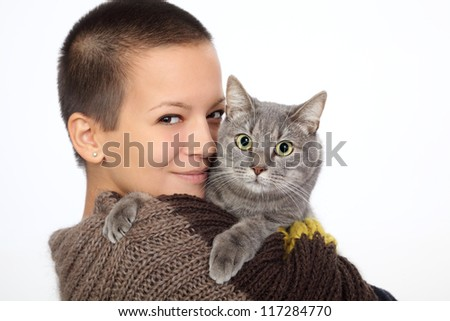 Young smiling woman hold gray domestic cat - stock photo