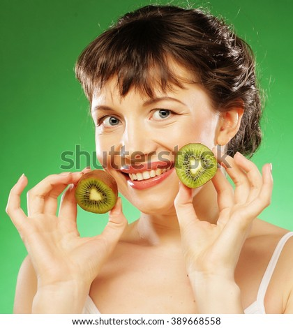 Young smiling woman holding kiwi.