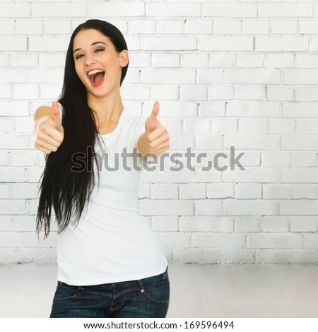 Young smiling woman holds her thumbs up against brick wall with copy space. Woman showing thumbs up sign. Focus on the face - stock photo