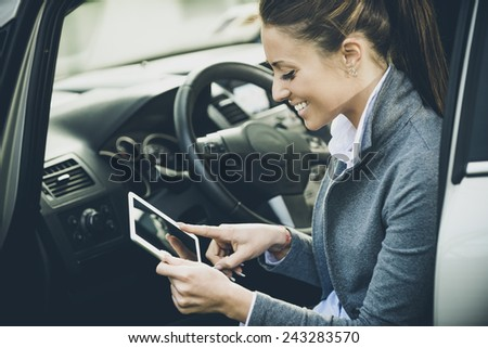 Young smiling woman in a car using a touch screen digital tablet. - stock photo