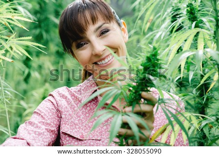 Young smiling woman in a hemp field checking plants and flowers, agriculture and nature concept - stock photo