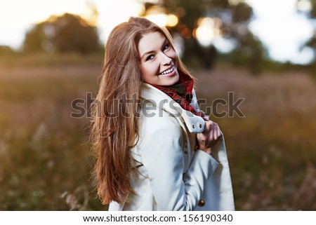 Young smiling woman in autumn field   - stock photo