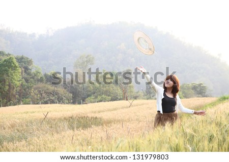 Young smiling woman in field with wheat