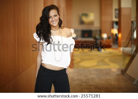 Young smiling woman in hotel lobby.