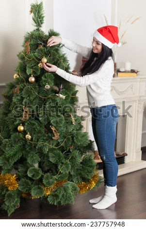 Young smiling woman in Santa hat decorating Christmas tree. - stock photo