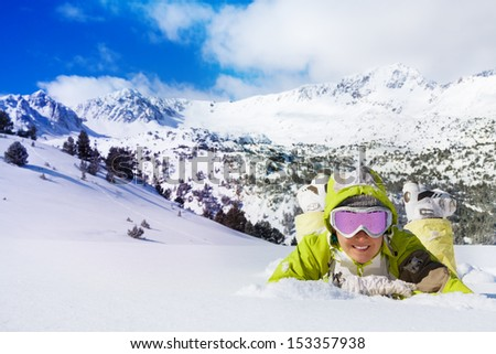 Young smiling woman in ski glasses laying in snow with mountain on background - stock photo