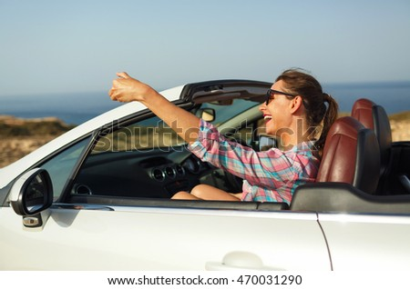 Young smiling woman in sunglasses making self portrait sitting in the cabriolet