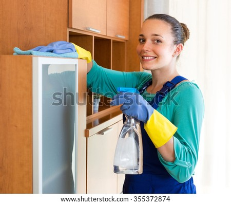 Young smiling woman in uniform making cleaning in the office-room   - stock photo