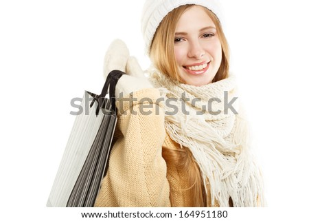Young smiling woman in warm winter clothing with bag standing isolated on white background - stock photo