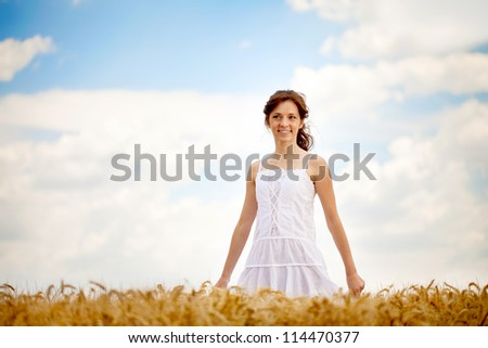 Young smiling woman in white dress in field with wheat