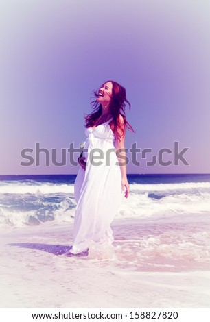 Young smiling woman in white dress standing in sea waves - stock photo