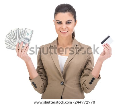 Young smiling woman is holding in hand a lot american dollars and credit card isolated on white background. - stock photo