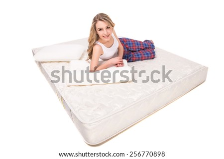 Young, smiling woman is lying on the quality mattress and looking at the camra, over white background. - stock photo