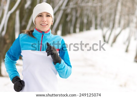 Young smiling woman jogging at winter morning in park. Happy running caucasian girl image with copy space - stock photo