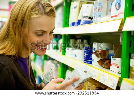young smiling woman looking at cosmetics in supermarket