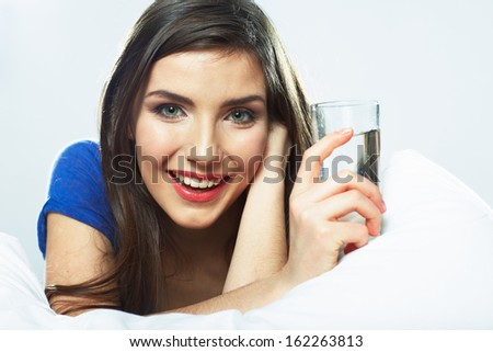 Young smiling woman lying in bed, hold water glass. Female model.