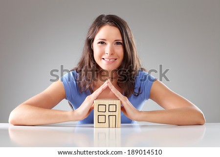 Young smiling woman make a roof with hands, symbolical - stock photo